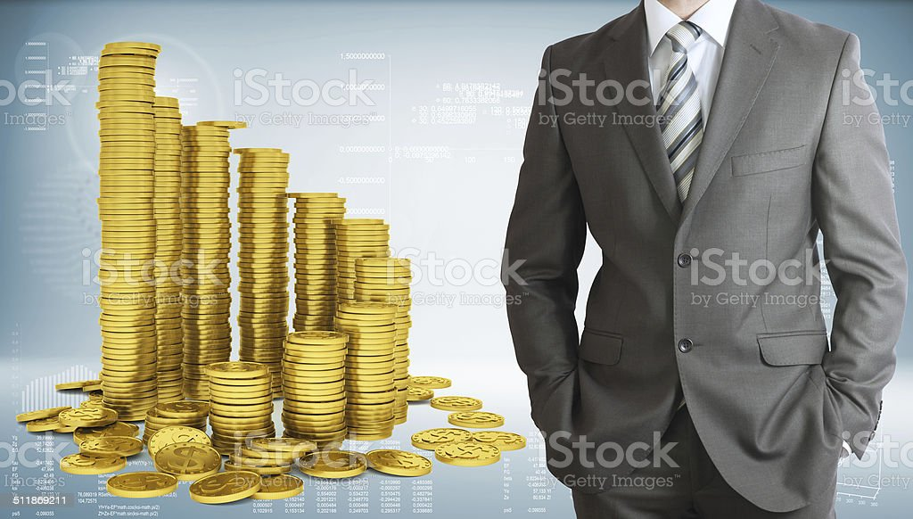 Businessman with pyramid of gold coins stock photo