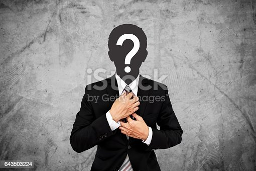 istock Businessman with question mark on head, on concrete wall background 643503224