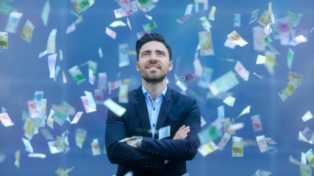 Businessman with raining banknotes stock photo