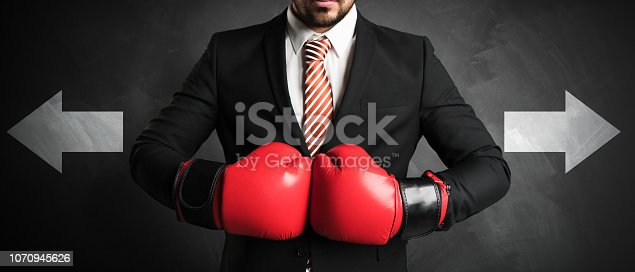 businessman with red boxing gloves in front of a chalkboard with two arrows