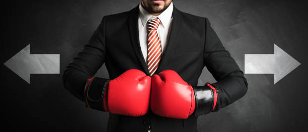 homme d'affaires avec des gants de boxe rouges - attestation photos et images de collection