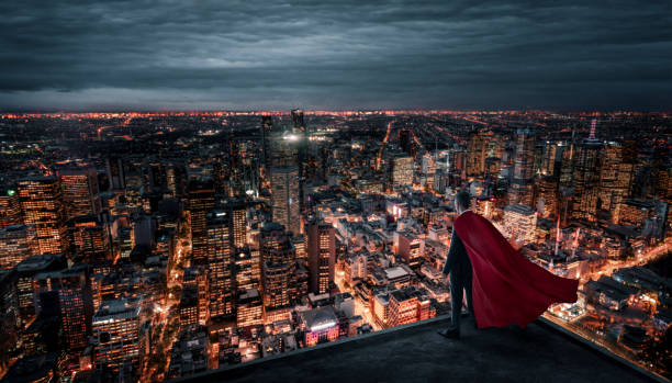 Businessman with red cape standing on the rooftop above the city at night stock photo