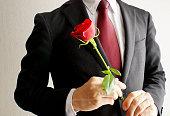 赤いバラの花を持つビジネスマン。