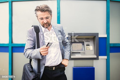 istock Businessman with rejected credit card next to cash machine. 543575974
