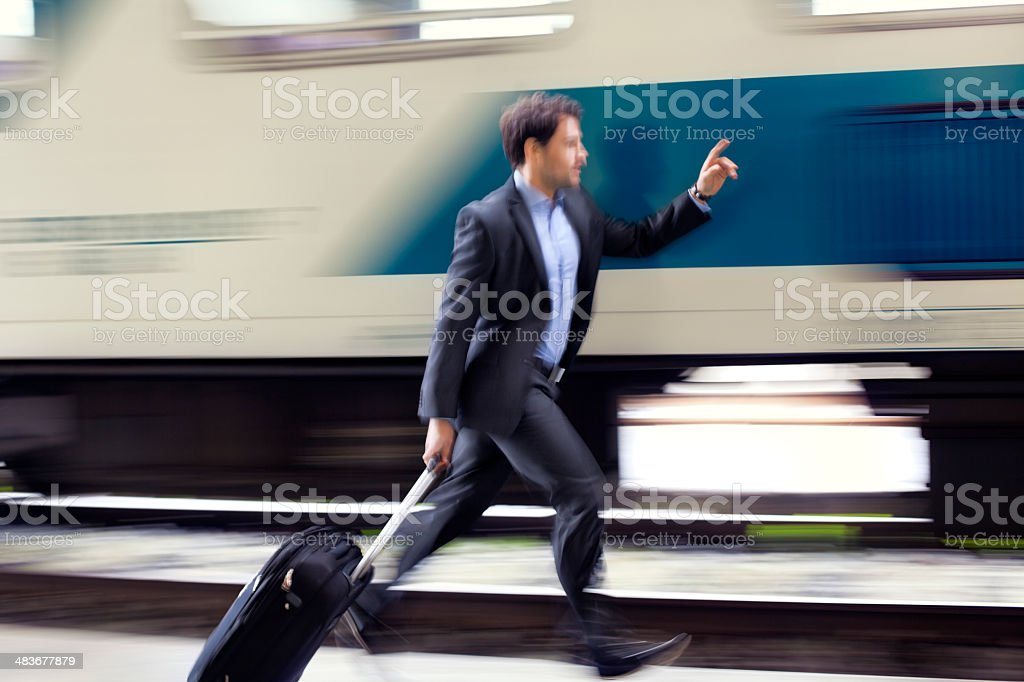 Businessman  with roller case Running For Train on Station Platform stock photo