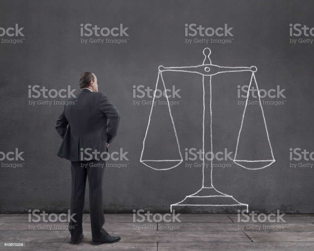 Businessman with Scales of Justice Sketched on the Wall Rear view of businessman standing on wooden floor with scales of justice sketched (chalk drawing) on the wall. Adult Stock Photo