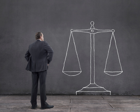 Businessman With Scales Of Justice Sketched On The Wall Stock Photo - Download Image Now