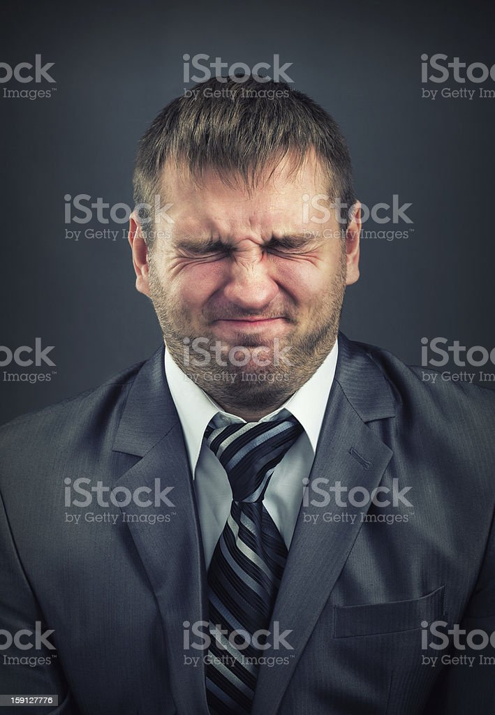 Businessman with screwed-up eyes stock photo