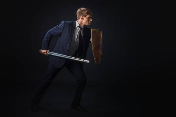 businessman with shield and sword in the fighting rack, free space on the right. anti-virus - sword zdjęcia i obrazy z banku zdjęć