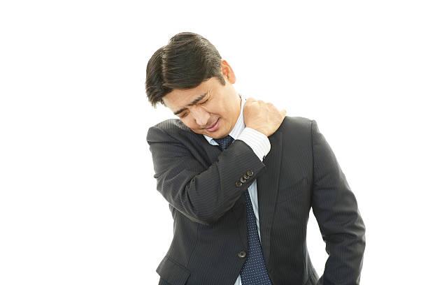 geschäftsmann mit schulterschmerzen. - schultersteife stock-fotos und bilder