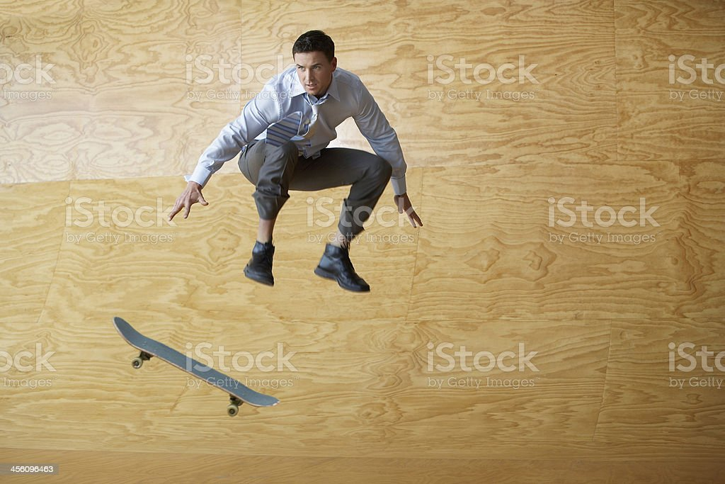Businessman With Skateboard Jumping Against Wood Paneling stock photo