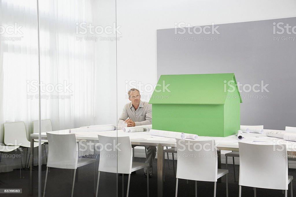 Biznesmen z małego modelu domu na Stół konferencyjny zbiór zdjęć royalty-free