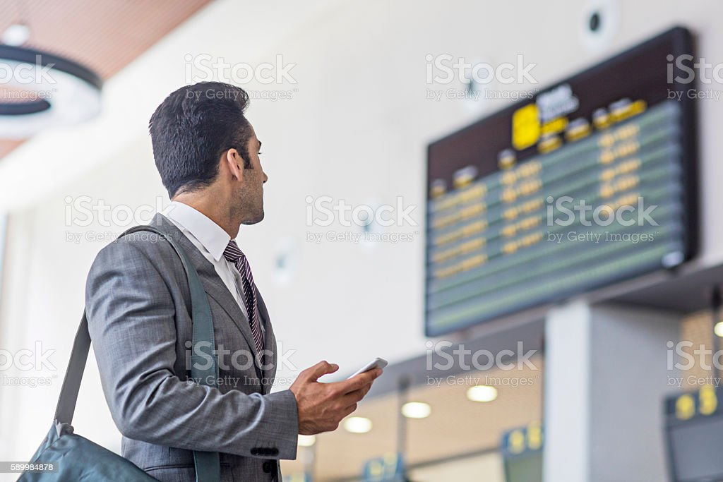 Businessman with smart phone checking arrival departure board stock photo