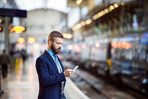 Businessman with smart phone Young handsome businessman with smart phone in subway subway platform stock pictures, royalty-free photos & images