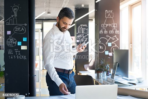 913346608 istock photo Businessman with smartphone and laptop in his office. 843280570