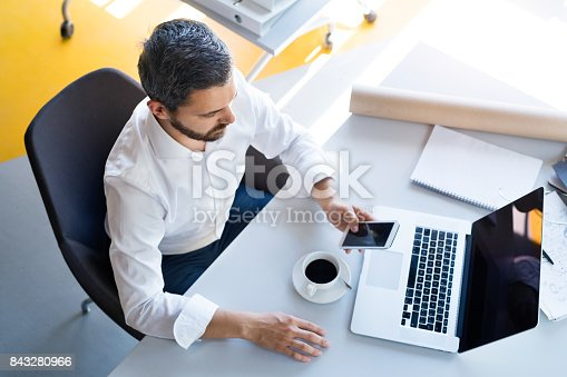 913346608 istock photo Businessman with smartphone and laptop in his office. 843280966