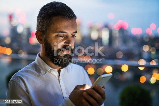 istock A businessman with smartphone at sunset, text messaging. 1053497202