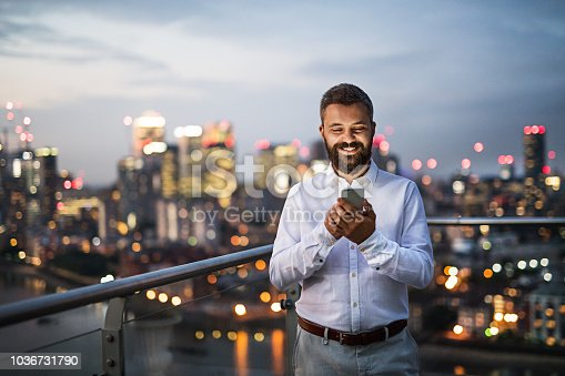 A portrait of businessman with smartphone standing against night London rooftop view panorama. Copy space.