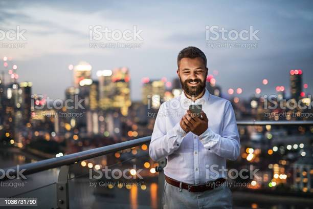 Photo of A businessman with smartphone standing against night London view panorama.