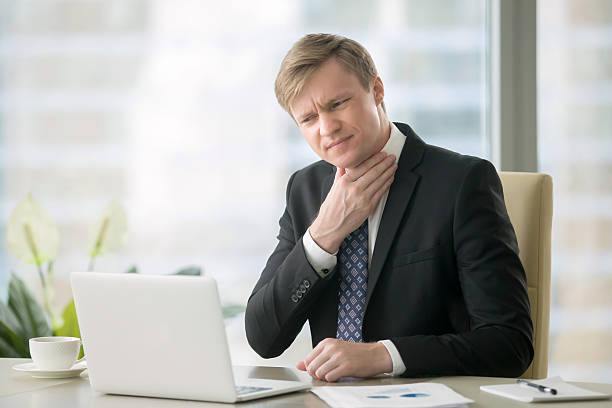 Businessman with sore throat Young businessman working with laptop at desk in the office, hand at his neck, feeling unwell, have a sore throat, after loud screaming, loss of voice, irritation, pain, and itchiness, hard to swallow heartburn throat pain stock pictures, royalty-free photos & images