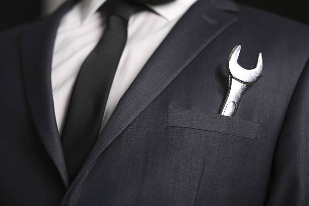 Businessman with spanner in his pocket stock photo
