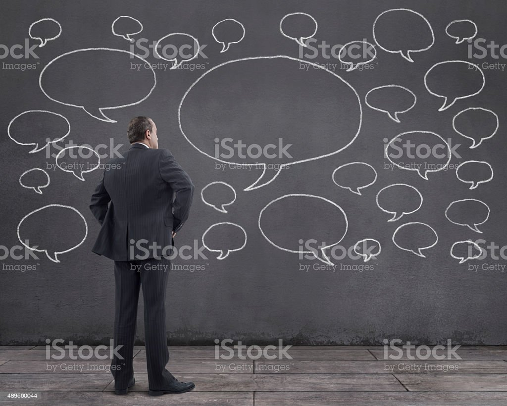 Businessman with Speech Bubbles Sketched on the Wall royalty-free stock photo