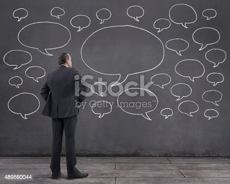 Businessman With Speech Bubbles Sketched On The Wall Stock Photo & More Pictures of 2015