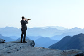 A businessman looks through a spyglass as he stands and looks out towards a series of mountain ridges that recede into the distance