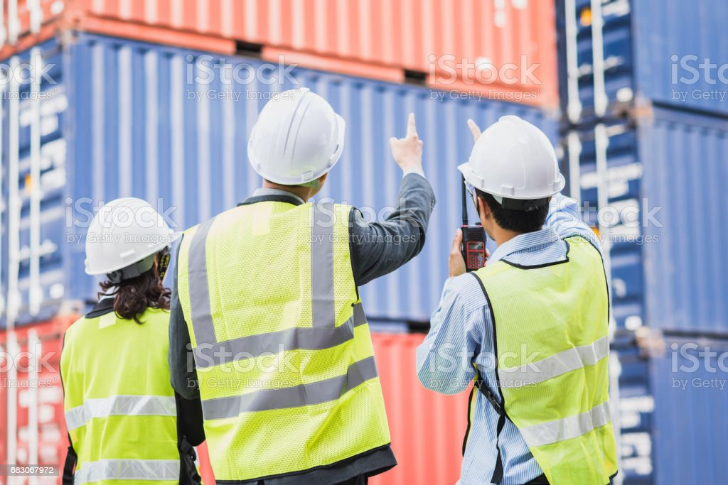 businessman with staff in logistic, export, import industry checking cargo container stock photo