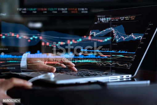 istock Businessman with statistic graph of stock market financial indices analysis on laptop screen, finance data and technology concept 868052824