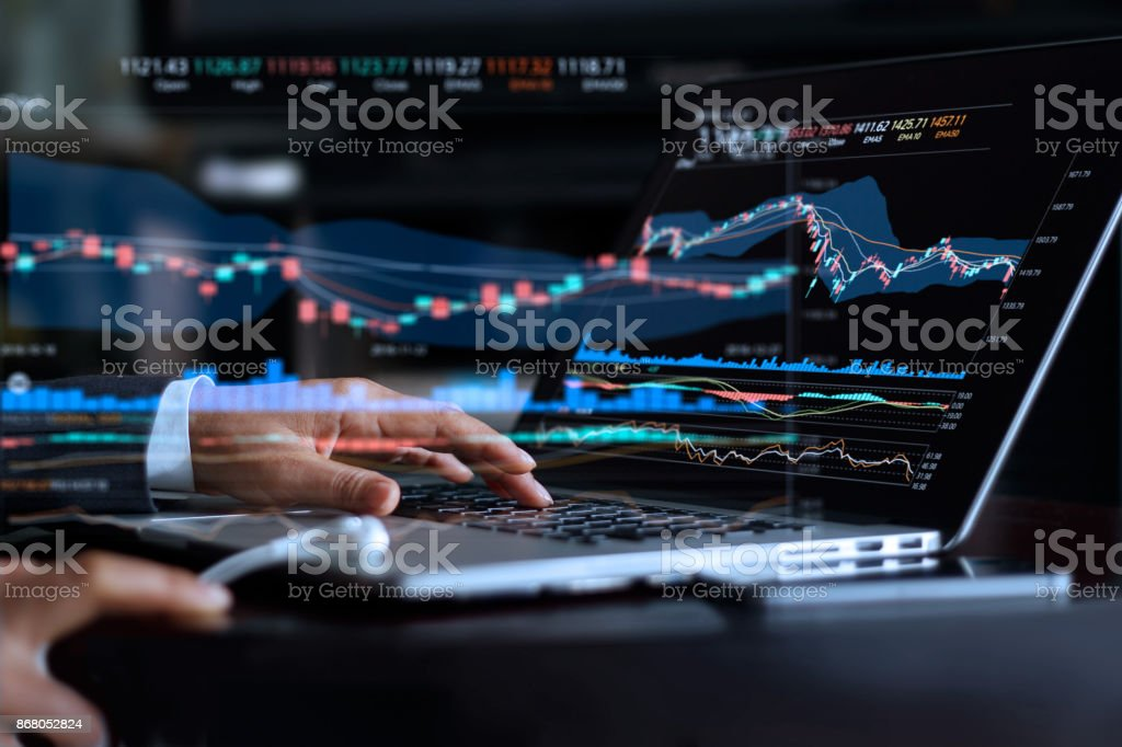 Businessman with statistic graph of stock market financial indices analysis on laptop screen, finance data and technology concept stock photo
