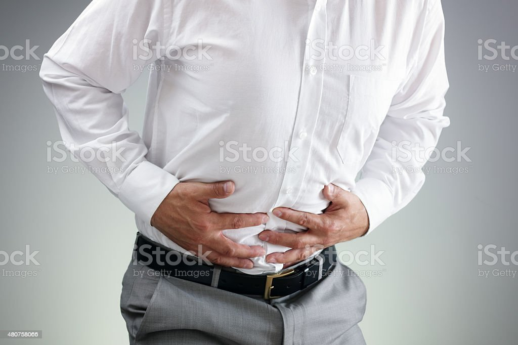 Businessman with stomach ache stock photo