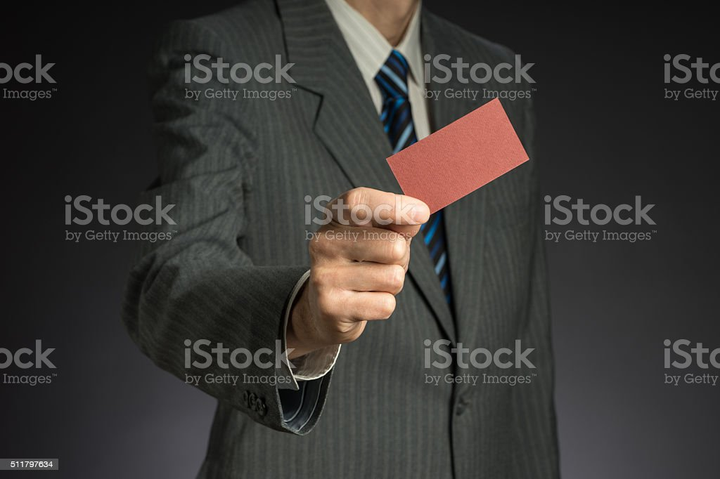 Businessman with suit stretching arm. Red business card in hand stock photo