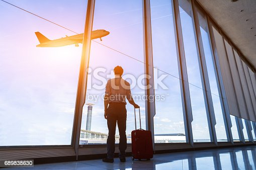 istock Businessman with suitcase at airport international departure gate, flying airplane 689838630