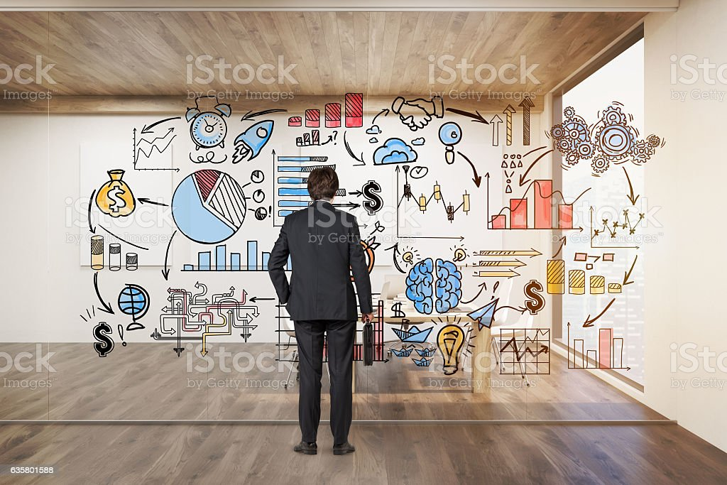 Businessman with suitcase looking at startup icons on glassboard stock photo
