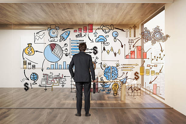 Businessman with suitcase looking at startup icons on glassboard - foto de acervo