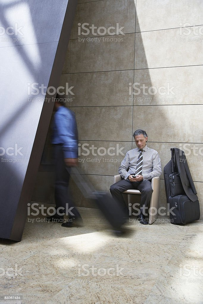 Businessman with suitcase using cell phone royalty free stockfoto