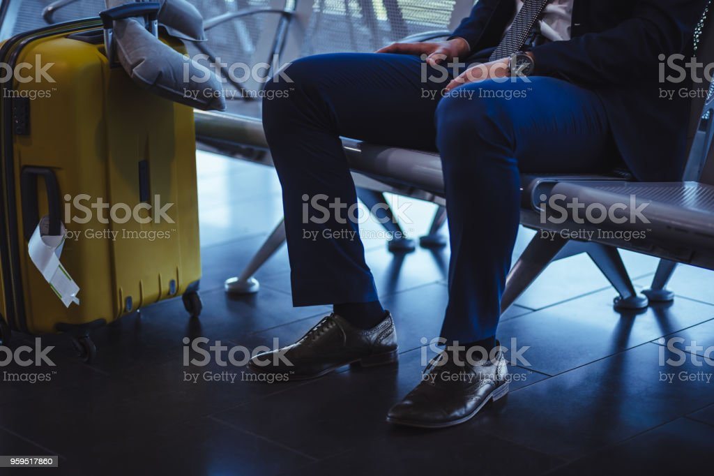 Businessman with suitcase waiting at airport departure area stock photo