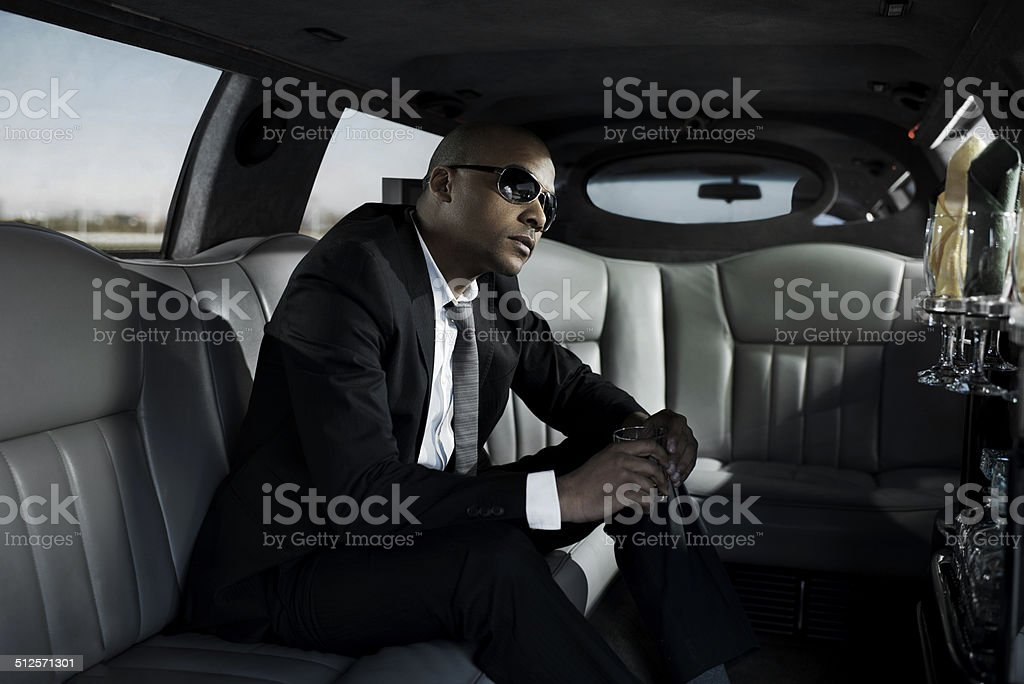 Businessman with sunglasses driving in a limousine. stock photo