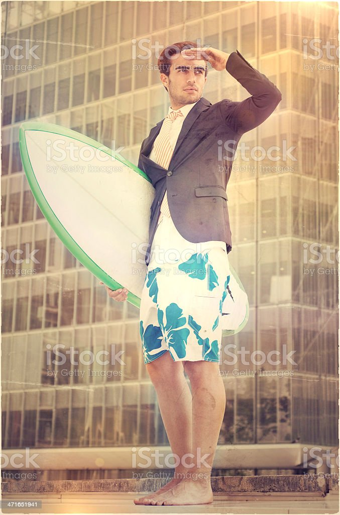 Businessman with surfboard and swimsuit looking away royalty-free stock photo