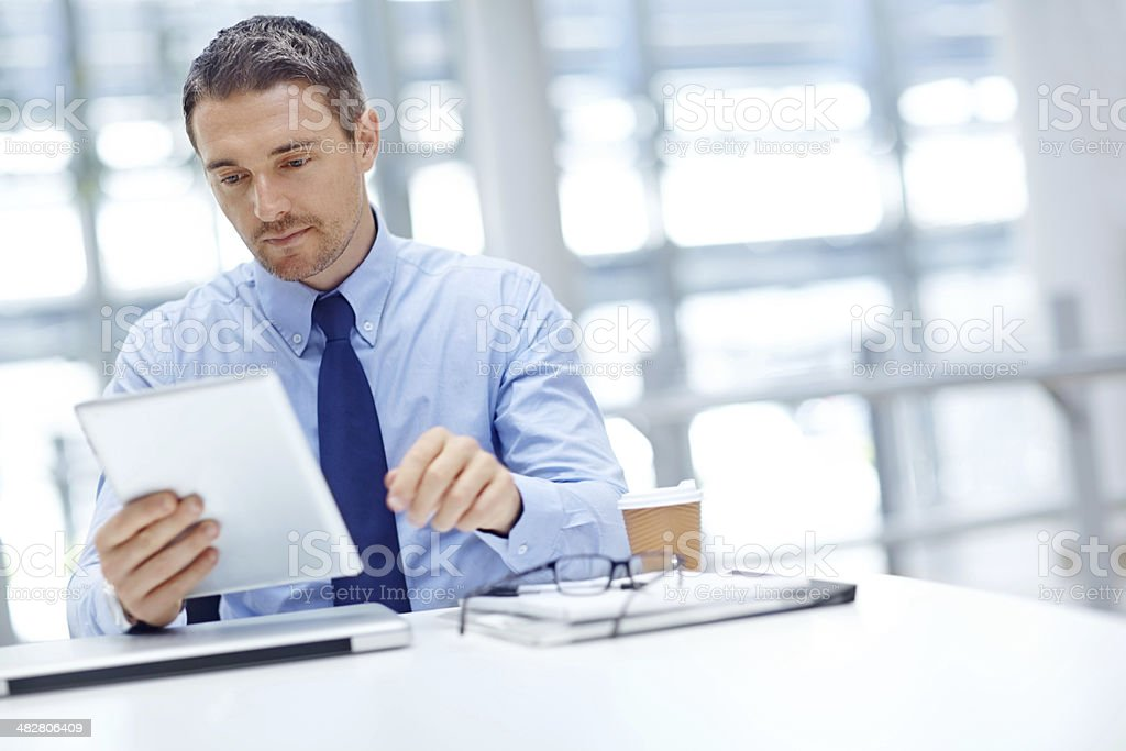 Businessman with tablet at office table stock photo