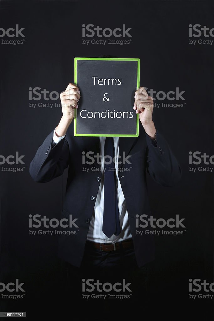 Businessman with terms and conditions written on slate stock photo