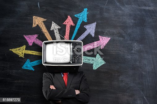 istock Businessman with TV head in front of blackboard 515597270