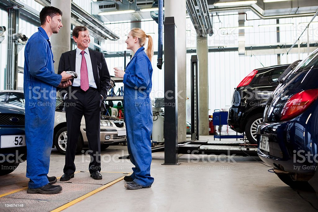 Businessman with two car mechanics in repair garage stock photo