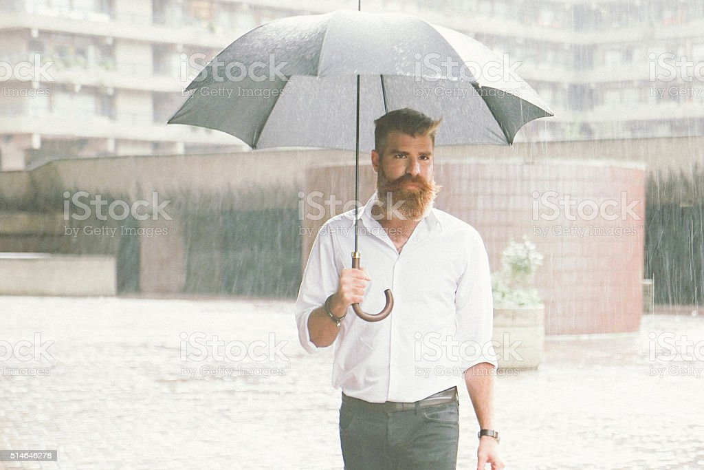 Businessman With Umbrella In The Rain stock photo
