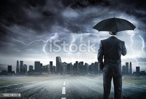istock Businessman With Umbrella Looking Storm Over City 1002182018