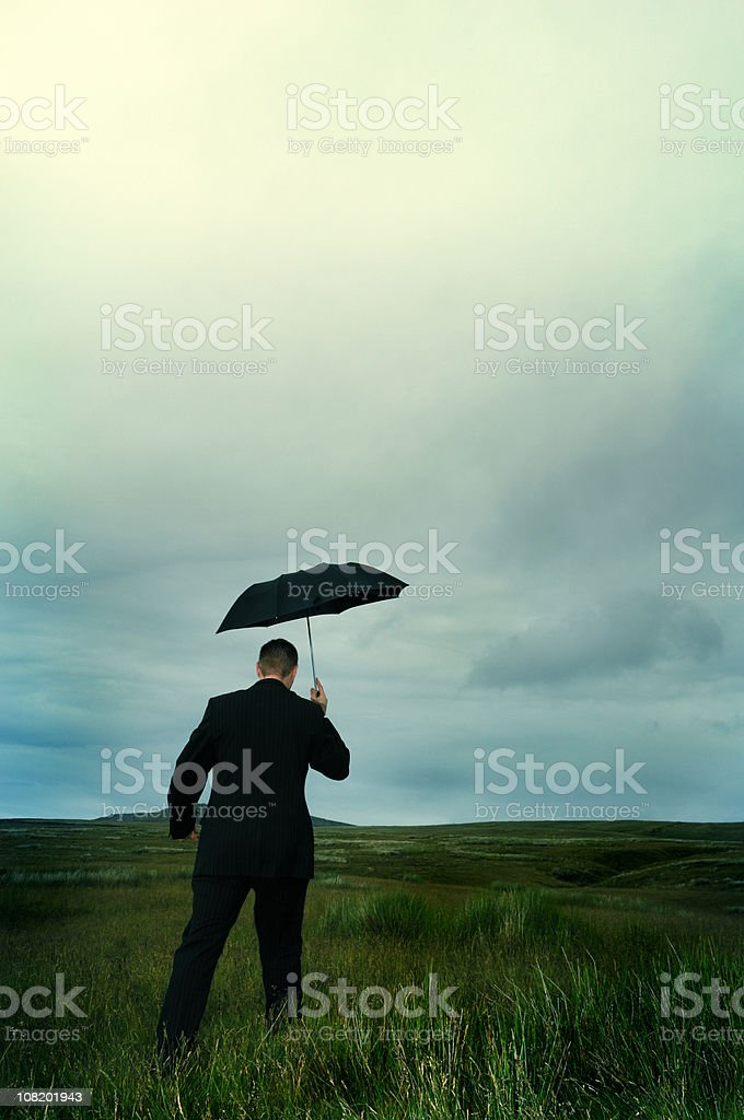 businessman with umbrella on stormy hillside royalty-free stock photo