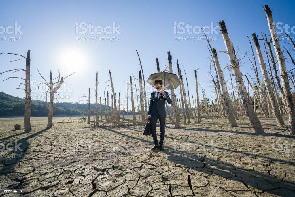 Empresário com pé de guarda-chuva na terra rachada - foto de acervo
