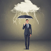 Businessman with umbrella under thunderstorm cloud