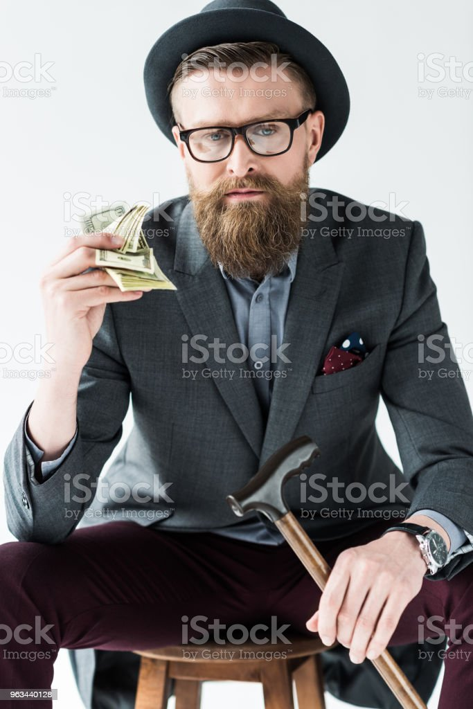 Businessman with vintage mustache and beard holding dollars isolated on light background - Zbiór zdjęć royalty-free (Banknot)